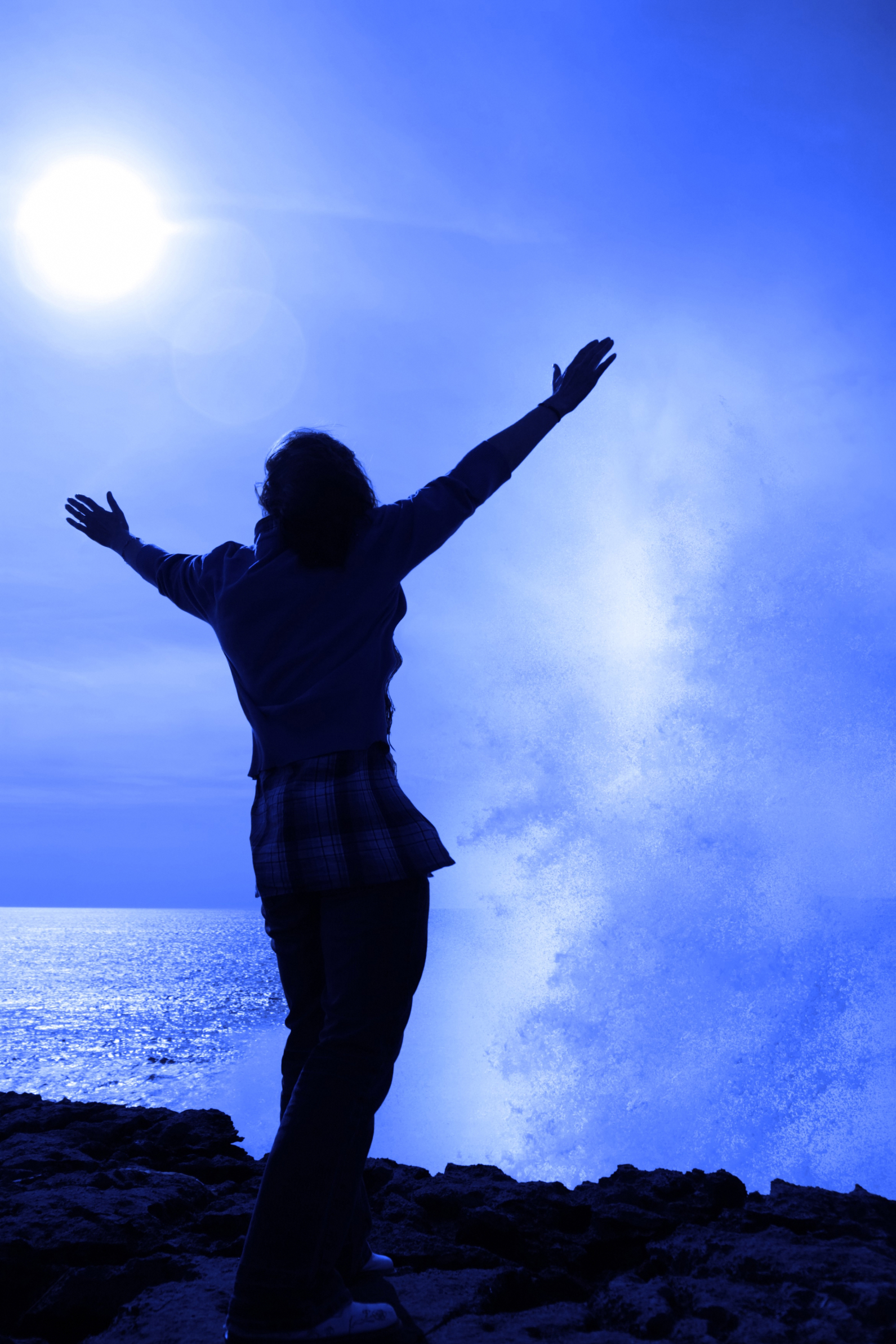a lone woman raising her arms in awe at the powerful wave on the cliffs edge