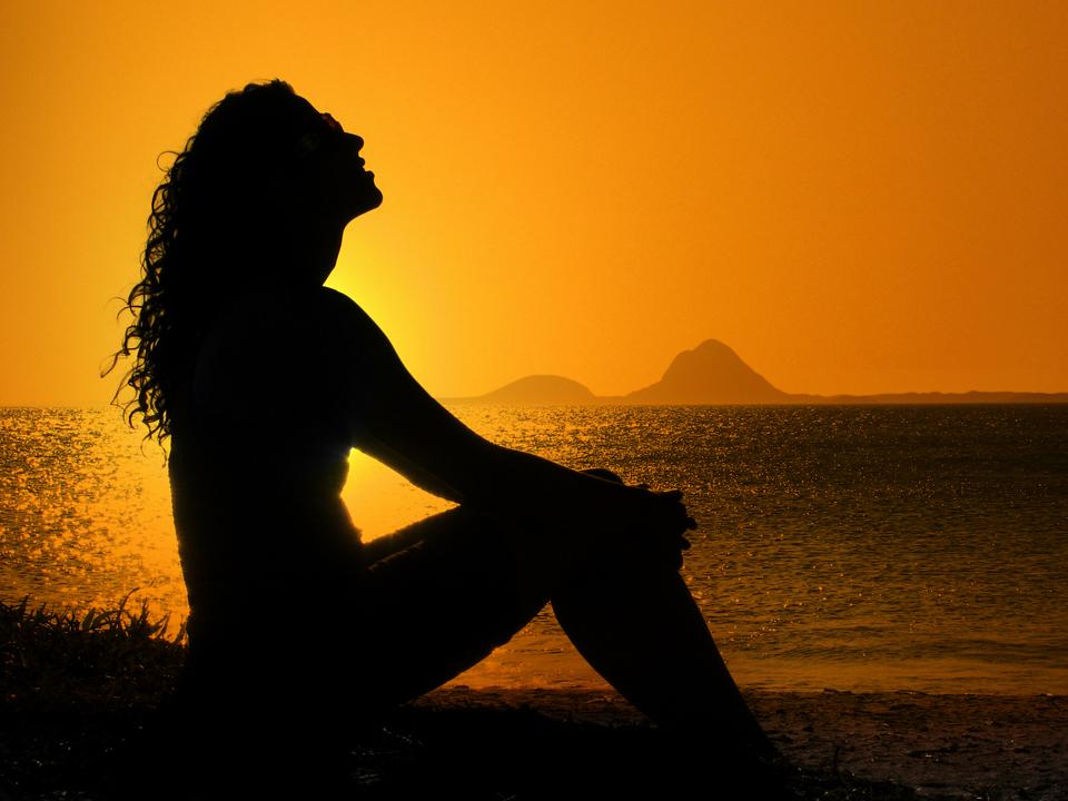 woman worshipping at sunset