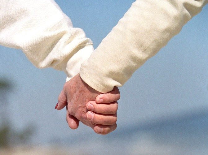 linked hands of 2 seniors who complete one another